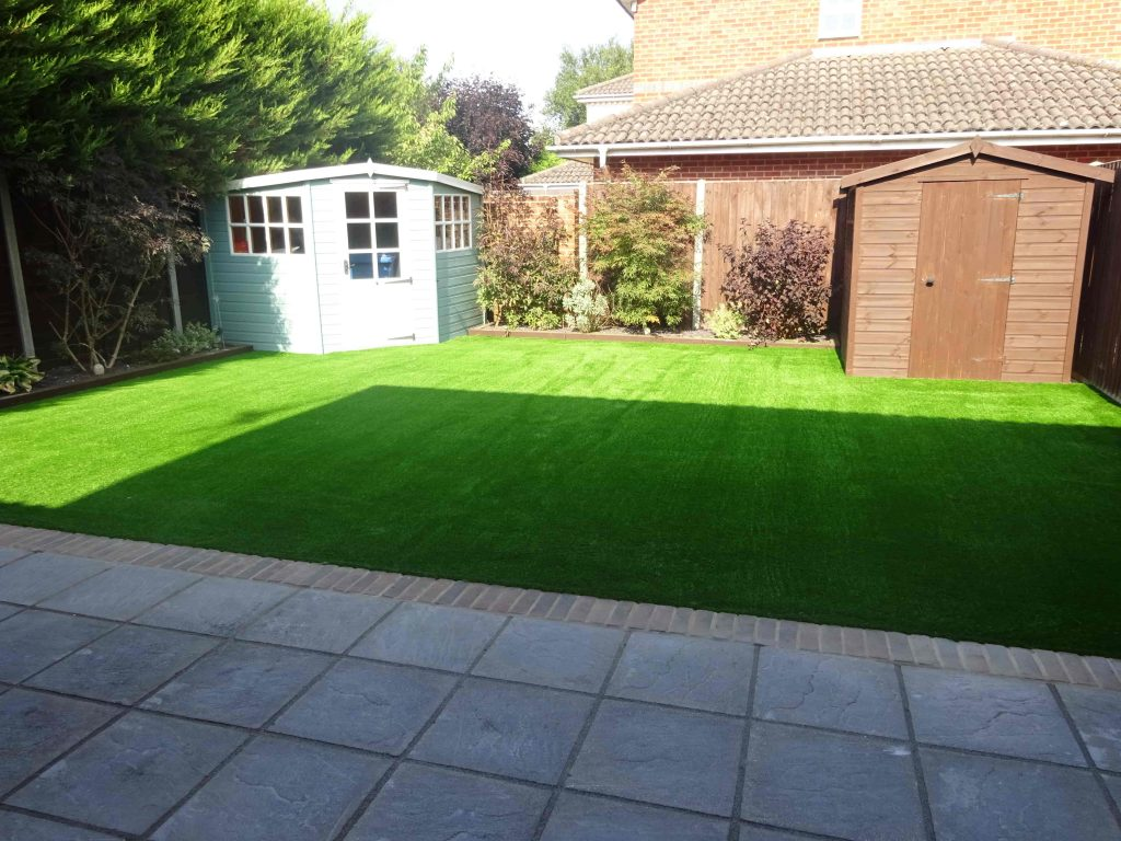 Freshly laid artificial grass and new patio by Acre Driveways