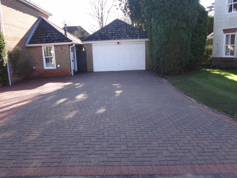Blue and red block paving leading to garage